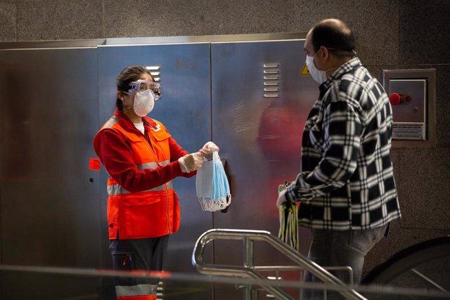 Una voluntaria de Cruz Roja, entidad socia de La Confederació, entrega mascarillas a los pasajeros en la estación de metro de Diagonal, en Barcelona (Catalunya, España), a 14 de abril de 2020.