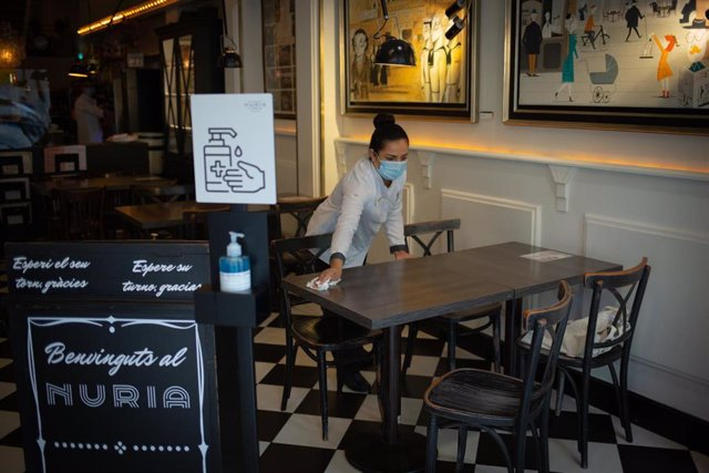 Una camarera limpia una mesa del histórico local barcelonés Núria.