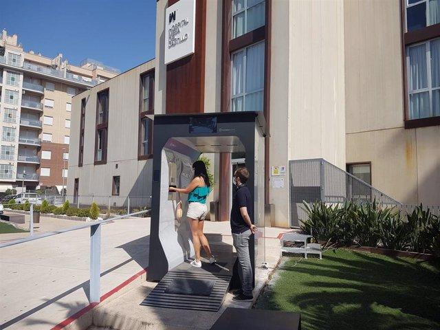 Una mujer pasa por el túnel de control y desinfección instalado en el Hospital Mesa del Castillo, en Murcia, por la empresa MaskGreen