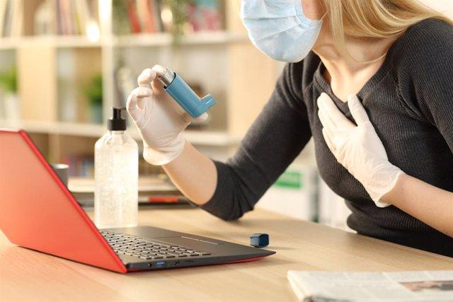 Mujer asmática con mascarilla, guantes e inhalador.