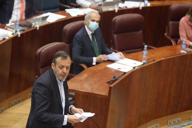 El consejero de Políticas Sociales de la Comunidad de Madrid, Albero Reyero (i), pasa por delante del consejero de Sanidad, Enrique Ruiz Escudero (d), durante una sesión plenaria en la Asamblea de Madrid en la que se debate la reprobación y cese de Ruiz E