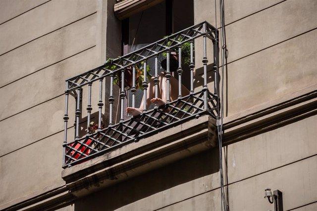 Una persona toma el sol en su balcón durante el tercer día de desconfinamiento de adultos y durante la fase 0 de la desescalada, en Barcelona/Catalunya (España) a 4 de mayo de 2020.