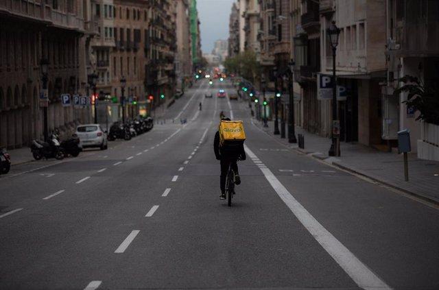 Un trabajador de Glovo en bicicleta por una calle de Barcelona, prácticamente vacía durante el primer día laborable de la segunda semana desde que se decretó el estado de alarma en el país a consecuencia del coronavirus, en Barcelona/Catalunya (España) a