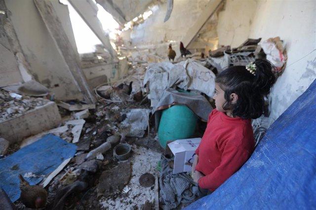 Dara, una niña desplazada siria, en una vivienda destrozada en Idlib