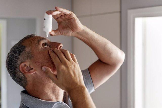 Hombre poniéndose colirio en el ojo.