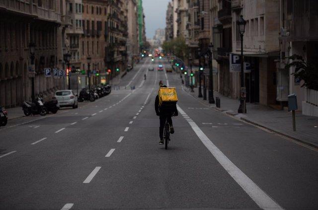 Un treballador de Glovo amb bicicleta per un carrer de Barcelona, pràcticament buida durant el primer dia laborable de la segona setmana des que es va decretar l'estat d'alarma al país a conseqüència del coronavirus, a Barcelona/Catalunya (Espanya)