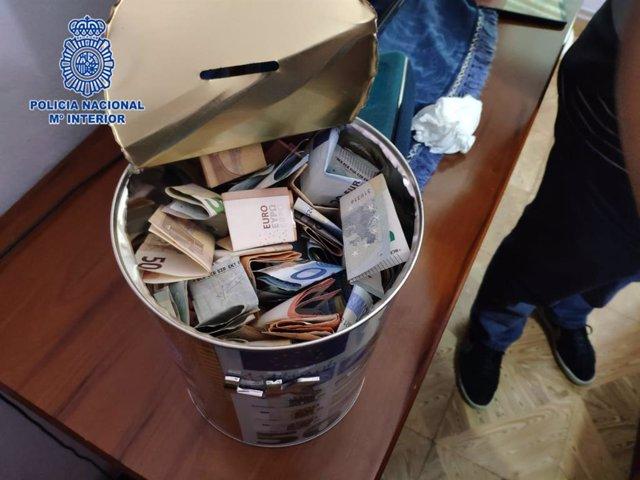 Cubo hucha con dinero incautado en el piso de unos traficantes de droga
