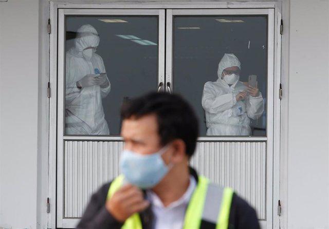 Trabajadores con trajes protectores en Tailandia.