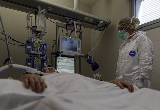 Personal sanitario totalmente protegido atiende a un paciente ingresado en la Unidad de Cuidados Intensivos del Hospital Infanta Sofía en San Sebastián de los Reyes (Madrid).