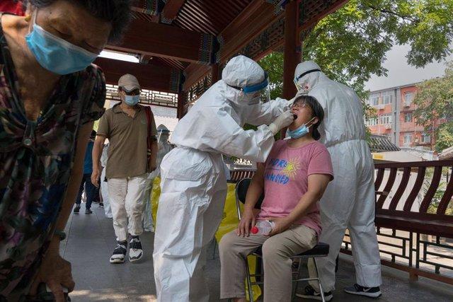 Una mujer se realiza la prueba de la COVID-19 en Pekín