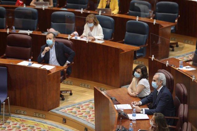 La presidenta de la Comunidad de Madrid, Isabel Díaz Ayuso (2d), el consejero de Sanidad, Enrique Ruiz Escudero (1d) y el consejero de Políticas Sociales, Alberto Reyero (3d), durante una sesión plenaria.