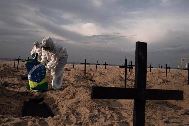 Activistas de la ONG Río en Paz durante un acto simbólico, criticando la gestión de la crisis sanitaria del Gobierno de Jair Bolsonaro con la representación de un cementerio en una de las playas del estado carioca.
