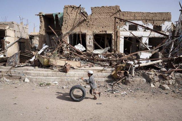 Un niño yemení delante de un edificio destruido.