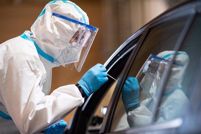 Un militar con traje de protección toma muestras a un conductor para una prueba de coronavirus en el distrito de Guetersloh, donde se sitúa el brote del matadero de Toennies