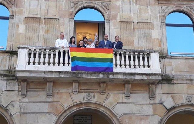 La alcaldesa de Gijón, Ana González, representantes municipales y de Xega descuelgan la bandera arcoíris en el Balcón Municipal, en 2019