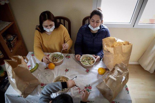 Dos mujeres y un niño durante la comida en su casa del barrio madrileño de Carabanchel
