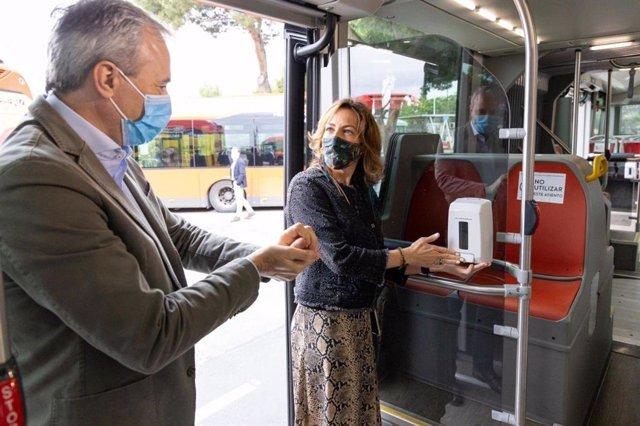 El alcalde de Zaragoza. Jorge Azcón, preuba un dispensador de gel en un autobús