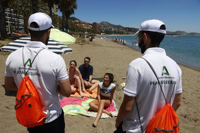 Una pareja de Vigilantes de la playa de Andalucía asesoran a bañistas sobre las medidas preventivas sobre el COVID-19 en la playa de La Malagueta. Málaga a 16 de junio del 2020