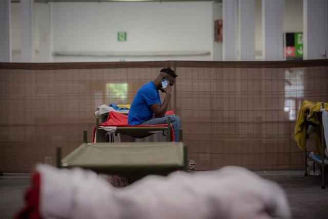 Un hombre consulta su móvil en su cama en el interior de las instalaciones del albergue de Fira Barcelona, habilitado por la crisis de la pandemia del coronavirus para 225 personas sin techo. En Barcelona, Catalunya (España), a 28 de mayo de 2020.