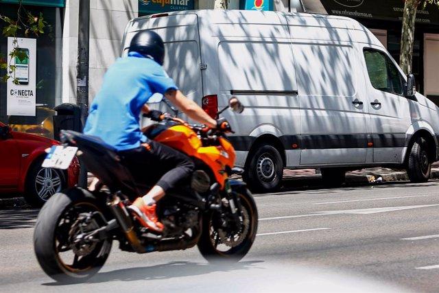 Un hombre circula en su moto por una calle de Madrid.