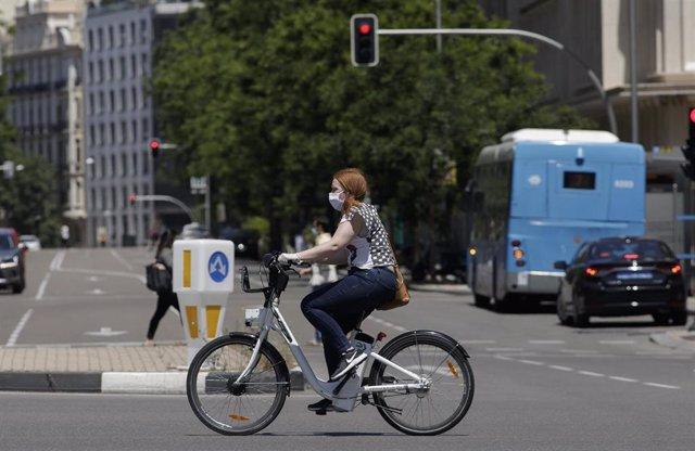 Una mujer protegida con mascarilla monta en una bicicleta de BiciMAD