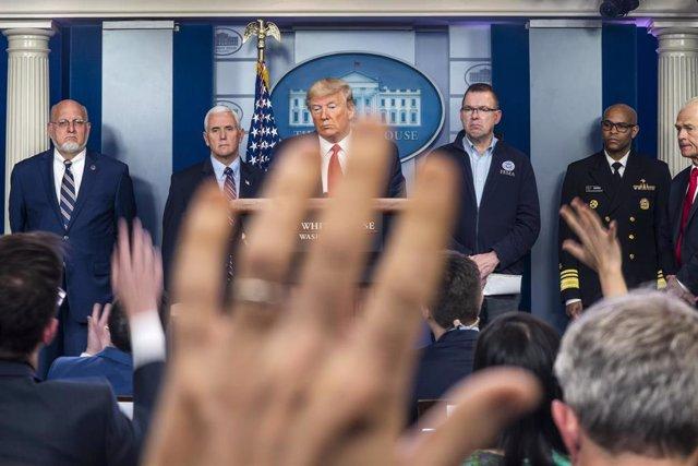 Robert Redfield, director de los CDC, a la izquierda de Mike Pence y Trump en una comparecencia en la Casa Blanca