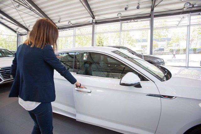 Una mujer abre un coche en un concesionario