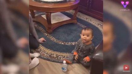 Un bebé de un año consigue que una botella de plástico dé unas cuantas vueltas en el aire antes de caer de pie