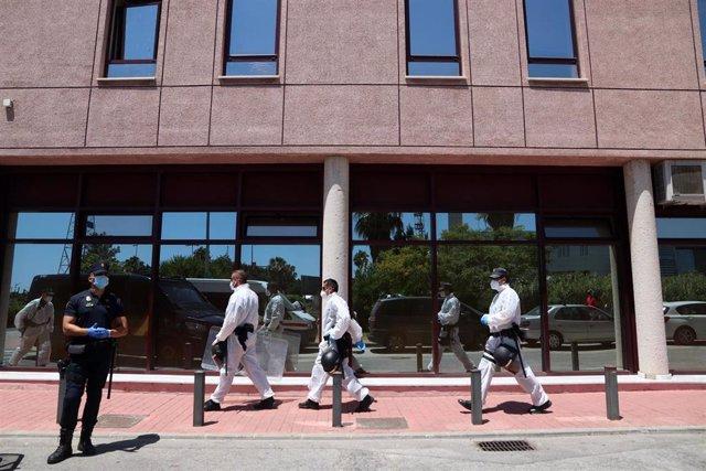 Agentes de la Policía Nacional equipados con Equipos de Protección Individual (EPI), custodian a contagiados de COVID-19 en una de las sede de Cruz Roja en Málaga, (Andalucía, España), a 25 de junio de 2020.