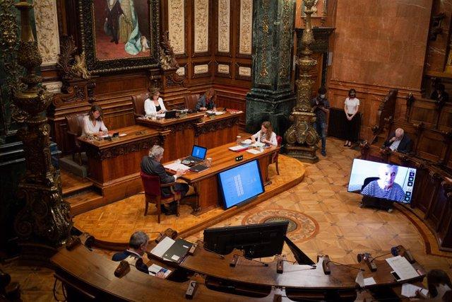 L'alcaldessa de Barcelona, Ada Colau (2i, en la taula del fons), durant la primera sessió plenària del Consell Municipal de l'Ajuntament de Barcelona després de la fi de l'estat d'alarma en la solament es compta amb la presència de 15 regidors.