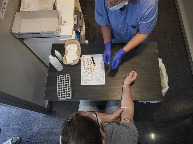 Una treballadora sanitària realitza una extracció de mostres per al garbellat i detecció d'anticossos (PCR), en una imatge d'arxiu