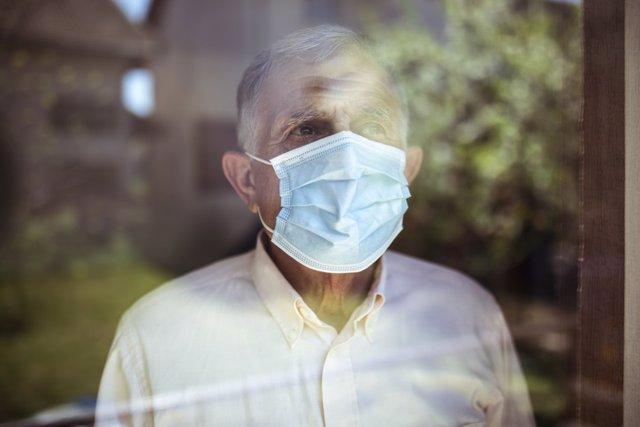 Hombre mayor mirando por la ventana con una mascarilla