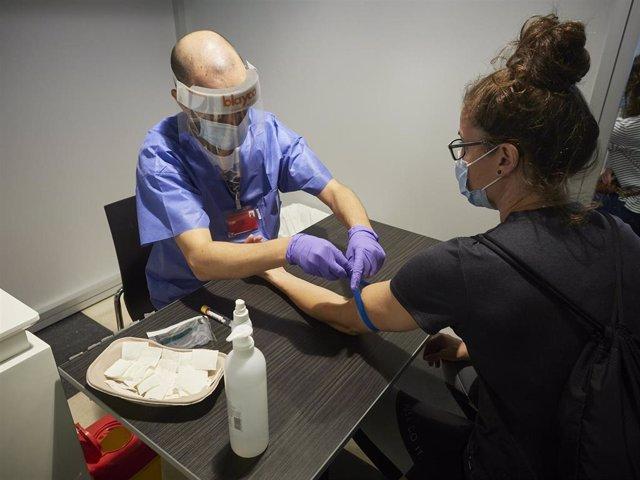 Un trabajador sanitario realiza una extracción de muestras en el recinto ferial REFENA de Pamplona para un programa  cribado y detección de anticuerpos.