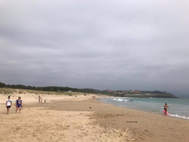 Personas en la playa en un día nublado.