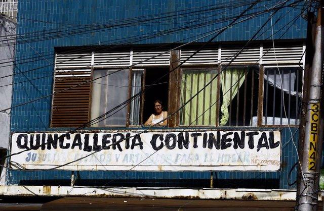 Una mujer mira a través de su ventana en medio de la pandemia del coronavirus.