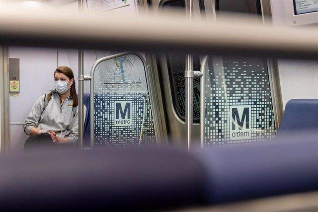Una mujer con mascarilla por el coronavirus en el metro de Washington.