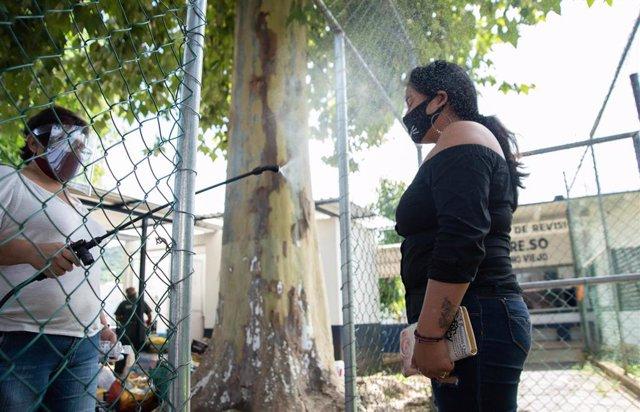 Imagen de un trabajador desinfectando a una mujer por el coronavirus en México.