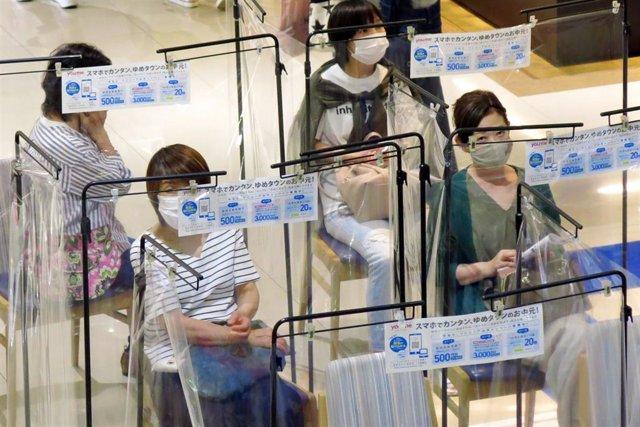 Mujeres con mascarilla haciendo cola para entrar en un centro comercial en Tokio
