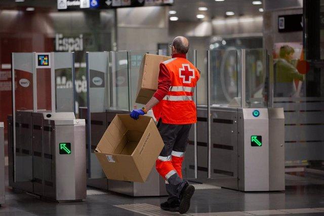 Un voluntario de Cruz Roja pasa por los tornos de la estación catalana de Diagonal con cajas vacías tras haber entregado mascarillas a los viajero.