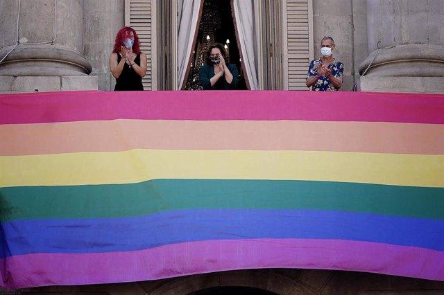 La alcaldesa de Barcelona, Ada Colau, con dos miembros LGBTI tras colgar la bandera del colectivo en la fachada del consistorio con motivo del Día del Orgullo 2020.