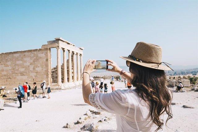 Un mujer hace una foto con su teléfono móvil en la Acropolis de Atenas (Grecia)