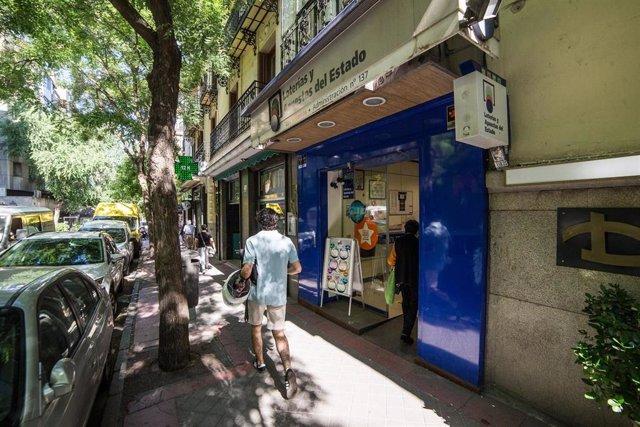 Un hombre pasa al lado de una administración de lotería abierta en la capital.