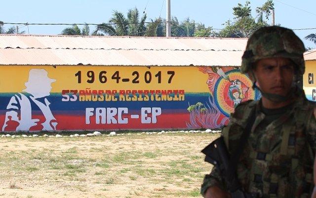 Un militar ante un mural de la guerrilla de las FARC