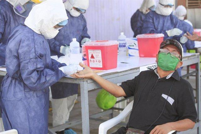 Personal médico somete a la prueba de la COVID-19 a un miembro de la comunidad indígena de Shipibo-Konibo, en Cantagallo, un asentamineto urbano de la capital peruana.