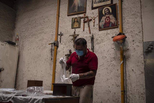 Un empleado del crematorio de San Isidro, en Ciudad de México, prepara las cenizas de una persona que falleció a causa de la COVID-19.