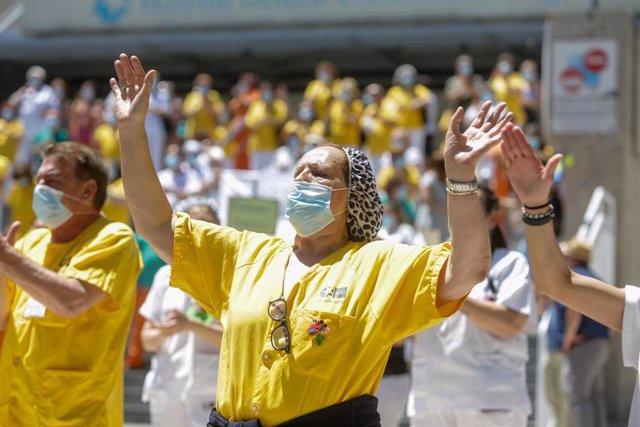 Una mujer levanta las manos durante la concentración convocada por las trabajadoras del servicio de limpieza del Hospital Gregorio Marañón de Madrid en protesta por la privatización de su servicio, en Madrid (España), a 22 de junio de 2020.