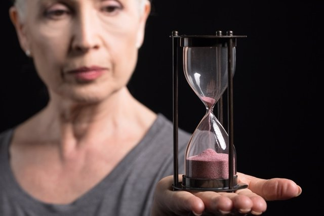 Senior woman holding sand clock isolated on black