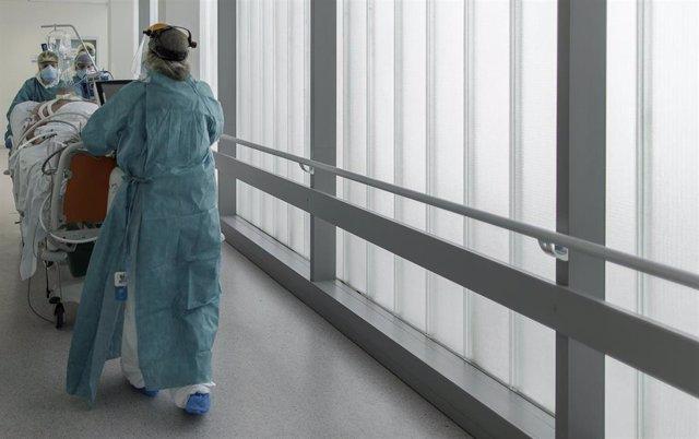 Personal sanitario totalmente protegido trasladan a un paciente (Archivo)