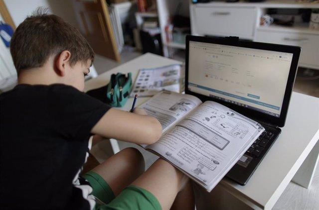 Un alumno de primaria hace los deberes de la asignatura de Inglés con varios libros y un ordenador