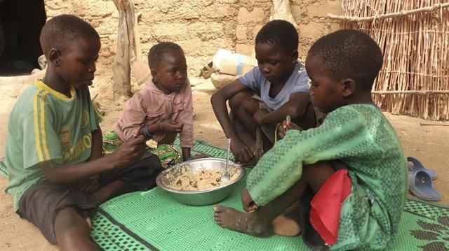 Uno niños comen alimentos suministrados por el PMA en Camerún